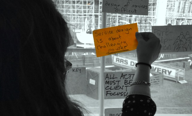 Post it note on a window with phrase service design is challenging power