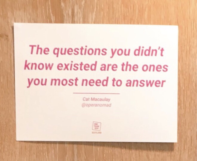 A poster on a wall, poster says the questions you didn't know existed are the ones you most need to answer.