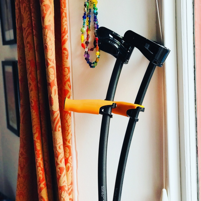 A pair of crutches, black with orange hand rests, leaning against a wall by a window.